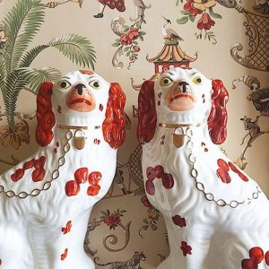 A pair of pottery Staffordshire dogs based on the Cavalier King Charles Spaniel breed.